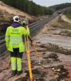 Tarjoamme asiakkaillemme mittausasiantuntijuutta kolmella kärjellä: tarkastus- ja valvontatoiminta, raiteenkartoitus ja mittausperustat. Kuvassa mies mittaa etäisyyttä rautatiellä.